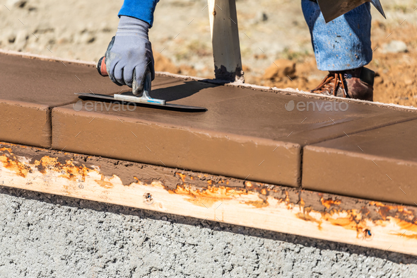 Construction Worker Using Trowel On Wet Cement Forming Coping Around New Pool - Stock Photo - Images