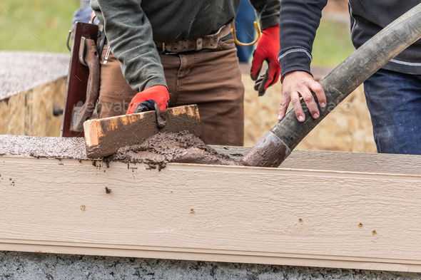 Construction Workers Pouring And Leveling Wet Cement Into Wood Framing - Stock Photo - Images