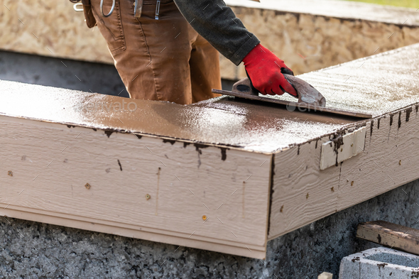 Construction Worker Using Wood Trowel On Wet Cement Forming Coping Around New Pool - Stock Photo - Images
