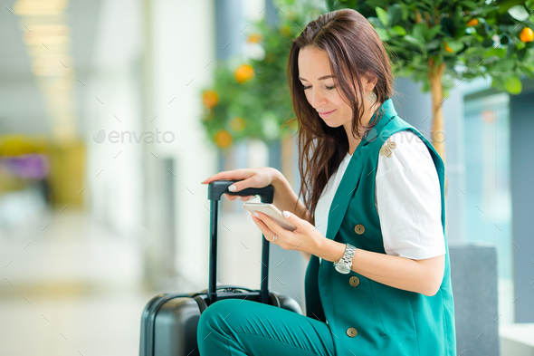 Portrait of young woman with smartphone in international airport. Airline passenger in an airport - Stock Photo - Images