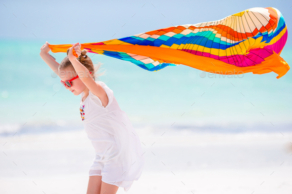 Little girl hve fun on the beach. Kid enjoy beach vacation with pareo - Stock Photo - Images
