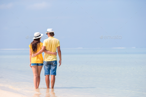 Happy family walking along the ocean on the beach - Stock Photo - Images