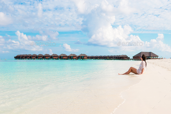 Young beautiful woman relaxing on beach during tropical vacation - Stock Photo - Images