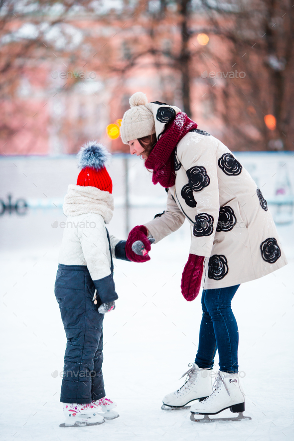 Little adorable girl with her mom skating on ice-rink - Stock Photo - Images