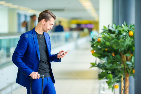 Young man in airport with baggage waiting boarding - Stock Photo - Images
