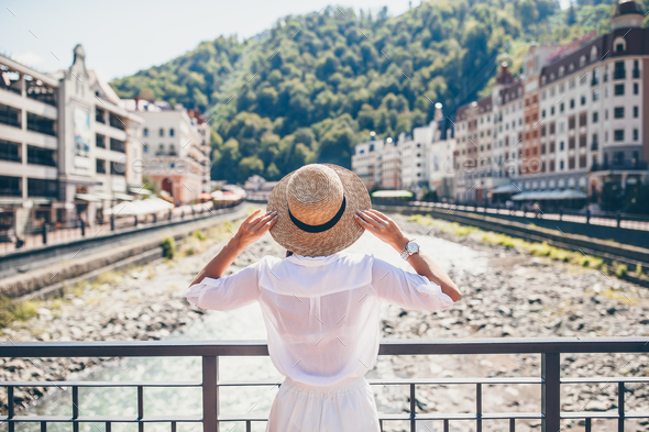 Happy girl at hat on the embankment of a mountain river in a European city - Stock Photo - Images
