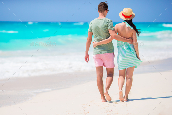 Young couple on white beach during summer vacation. Happy family enjoy their vacation - Stock Photo - Images