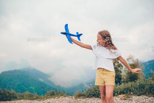 Beautiful happy little girl in mountains in the background of fog - Stock Photo - Images