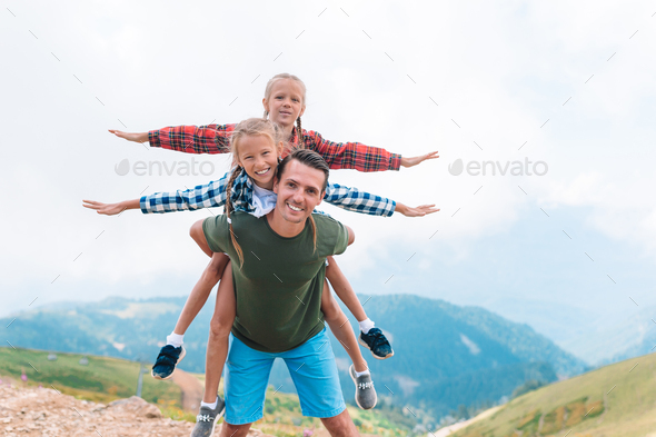 Beautiful kids and happy man in mountains in the background of fog - Stock Photo - Images