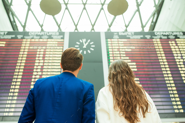 Young man and woman in international airport looking at the flight information board - Stock Photo - Images