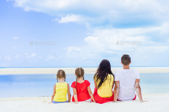 Happy family of four on beach vacation - Stock Photo - Images