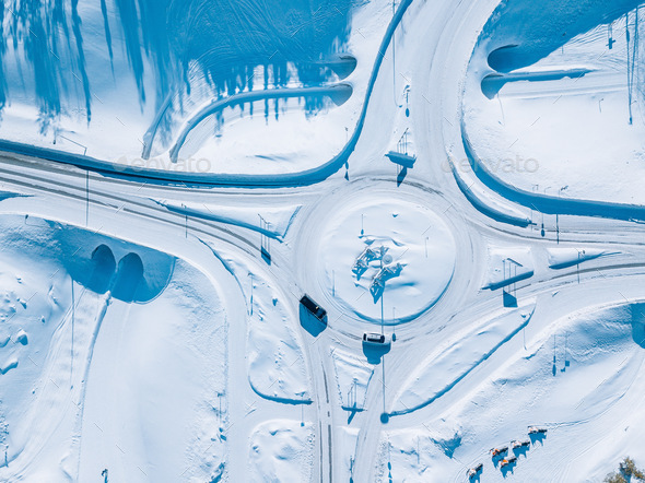 Aerial view of roundabout road intersection with snow winter road with a circular motion - Stock Photo - Images