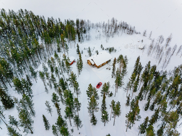 Aerial view of wooden log cabin or cottage in snow  winter forest by the lake in rural Finland - Stock Photo - Images