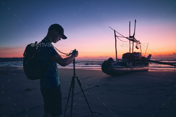 Photographer on beach at beautiful sunrise - Stock Photo - Images
