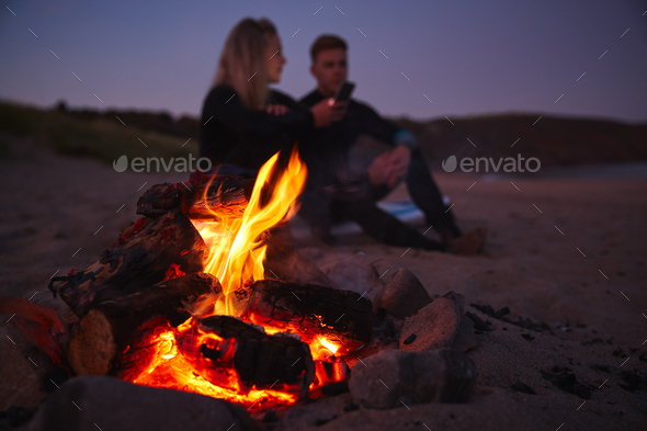 Couple Sitting On Surfboard By Camp Fire On Beach Using Mobile Phone As Sun Sets Behind Them - Stock Photo - Images