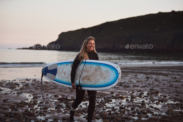 Woman Wearing Wetsuit Carrying Surfboard As She Walks Out Of Sea - Stock Photo - Images