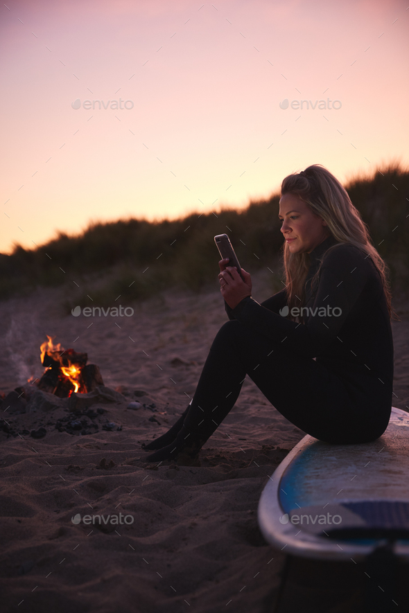Woman Sitting On Surfboard By Camp Fire On Beach Using Mobile Phone As Sun Sets Behind Her - Stock Photo - Images