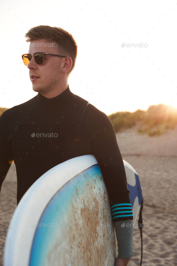 Young Man In Sunglasses Wearing Wetsuit Enjoying Surfing Staycation On Beach As Sun Sets - Stock Photo - Images