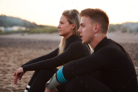 Profile View Of Couple Wearing Wetsuits On Surfing Staycation Sitting On Beach Looking Out To  Sea - Stock Photo - Images