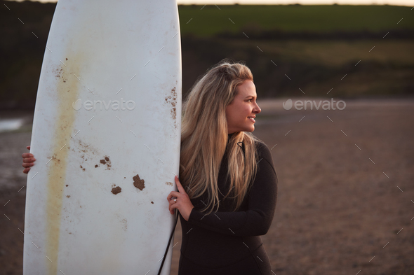 Woman Wearing Wetsuit Holding Surfboard Enjoying Surfing Staycation On Beach As Sun Sets - Stock Photo - Images