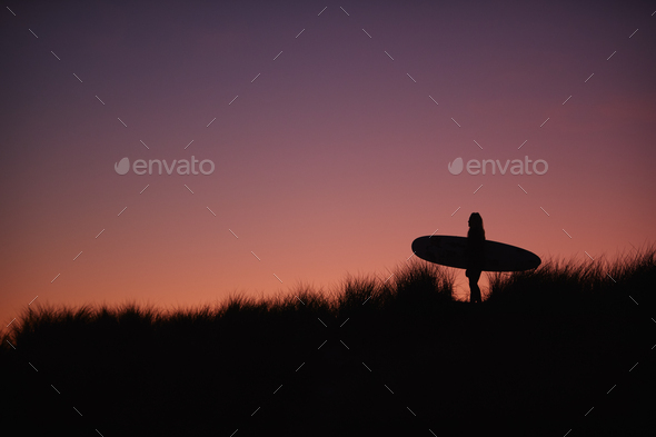 Silhouette Of Female Surfer Carrying Surfboard Across Dunes Against Setting Sun - Stock Photo - Images
