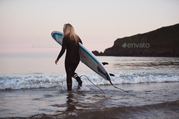 Woman Wearing Wetsuit Carrying Surfboard As She Walks Into Sea - Stock Photo - Images