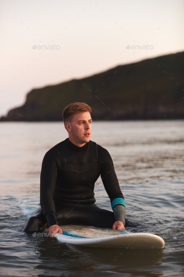 Man Wearing Wetsuit Sitting And Floating On Surfboard On Calm  Sea - Stock Photo - Images