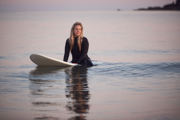 Woman Wearing Wetsuit Sitting And Floating On Surfboard On Calm  Sea - Stock Photo - Images