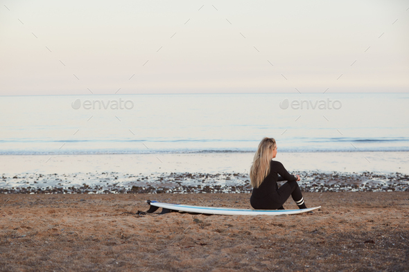 Rear View Of Thoughtful Woman Wearing Wetsuit On Surfing Staycation Looking Out To  Sea At Waves - Stock Photo - Images