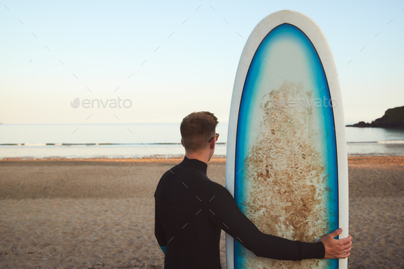Rear View Of Young Man Wearing Wetsuit Enjoying On Surfing Staycation Looking Out To  Sea At Waves - Stock Photo - Images