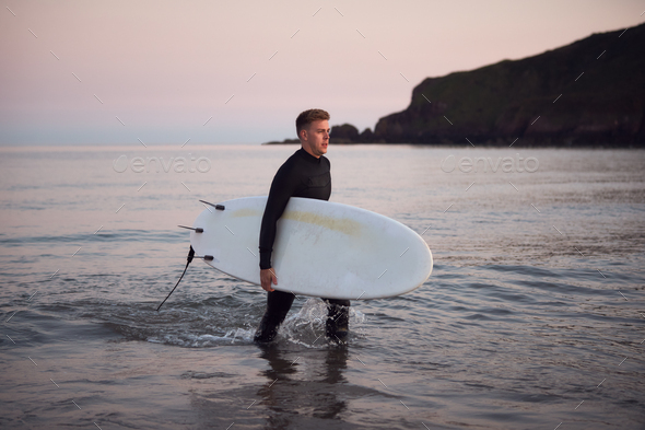 Man Wearing Wetsuit Carrying Surfboard As He Walks Out Of Sea - Stock Photo - Images
