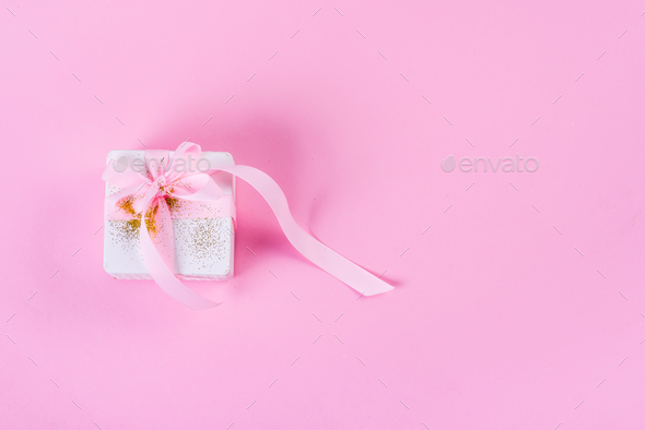 White gift box tied with pink ribbon on pink pastel background with copy space - Stock Photo - Images