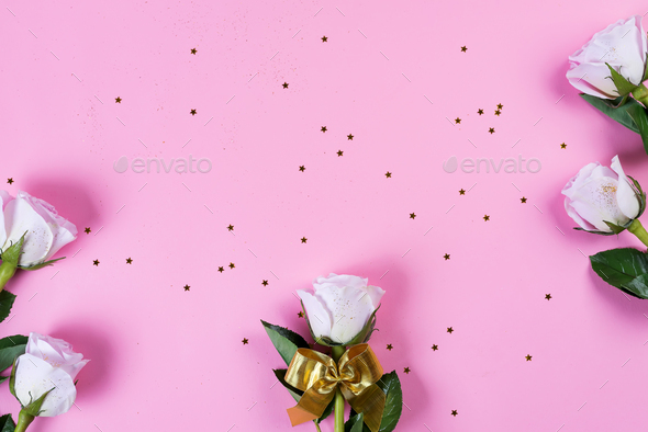 Pink roses flowers with gold bow and gold glitter on a pink background, flat lay - Stock Photo - Images
