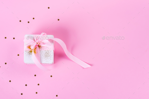 Gift or present box with confetti stars and pink ribbon on pastel pink background. Holiday pattern - Stock Photo - Images