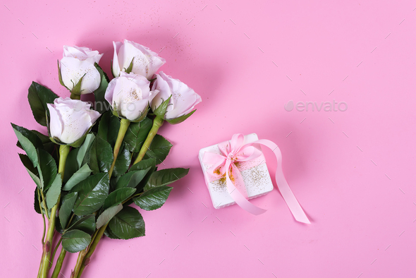 Pink rose and white gift box with pink ribbon on pink background - Stock Photo - Images