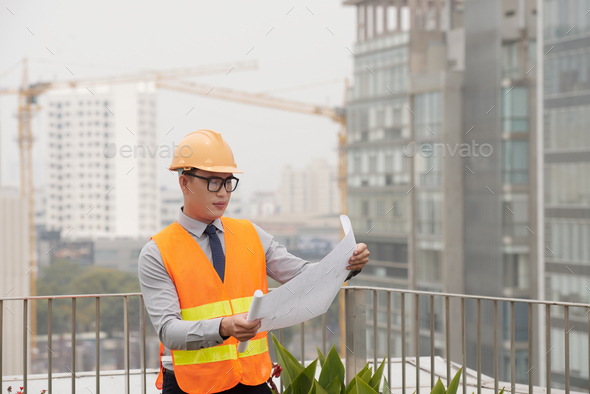 Examining blueprint - Stock Photo - Images