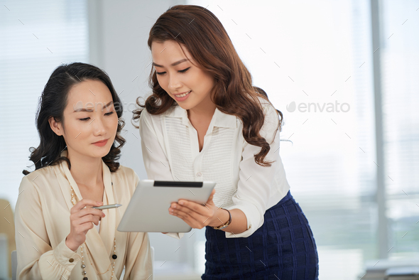 Showing business document to colleague - Stock Photo - Images