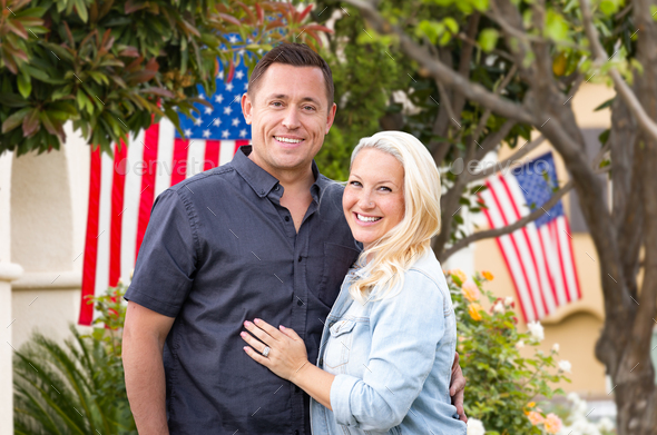 Happy Couple In Front of Houses with American Flags - Stock Photo - Images