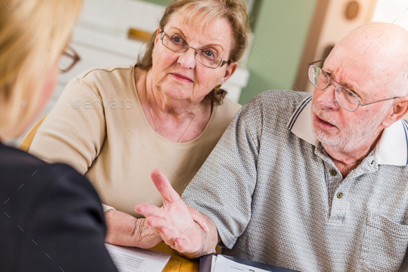 Senior Adult Couple Going Over Documents in Their Home with Agent At Signing - Stock Photo - Images