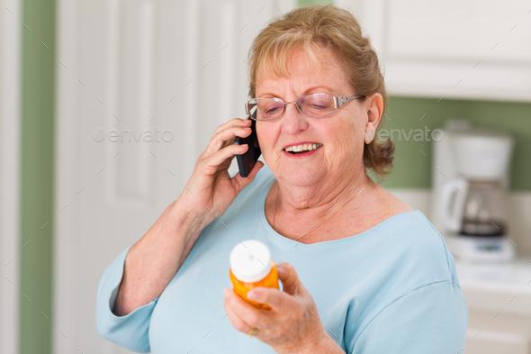 Senior Adult Woman on Cell Phone Holding Prescription Bottle - Stock Photo - Images