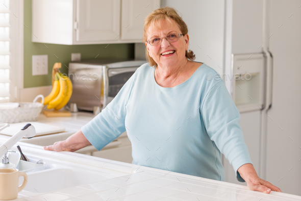 Portrait of A Beautiful Smiling Senior Adult Woman in Kitchen - Stock Photo - Images