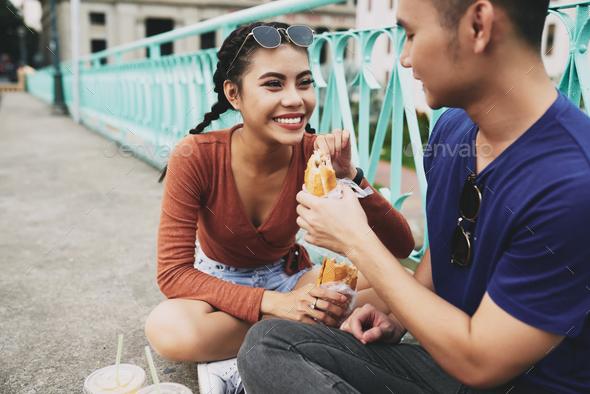 Couple enjoying sandwiches - Stock Photo - Images