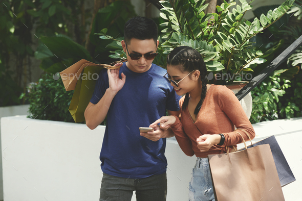 Young couple checking phone - Stock Photo - Images