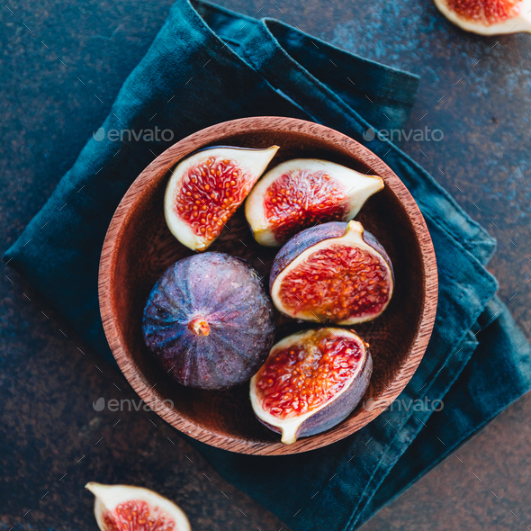 Top view of ripe quartes figs in a wooden small bowl on a table. - Stock Photo - Images