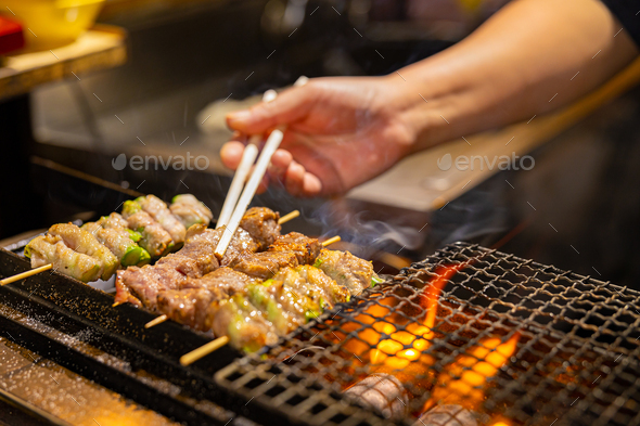 Vendor preparing meat on barbecue grill in Japan - Stock Photo - Images