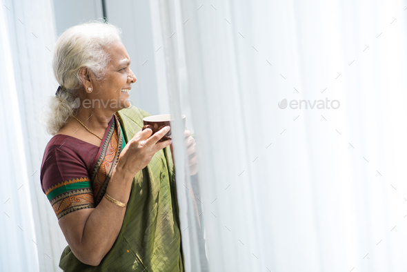 Aged woman looking throug window - Stock Photo - Images