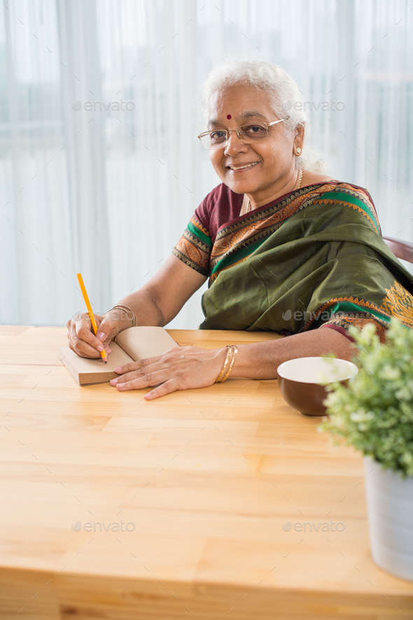 Smiling woman writing down ideas - Stock Photo - Images