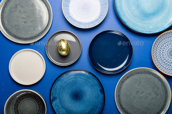 Different Plates with Easter Egg on blue background - Stock Photo - Images