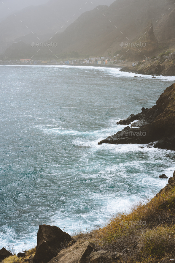 Rough ocean waves with blowing spray rolling onto the rocky volcanic shore. Paul Pombas place near - Stock Photo - Images