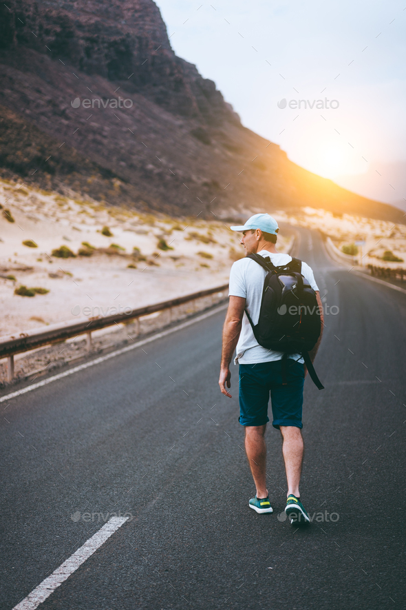 Traveler with backpack walks in the center of an epic winding road. Huge volcanic mountains in the - Stock Photo - Images